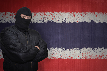 middle east crisis: dangerous man in a mask standing near a wall with painted national flag of thailand
