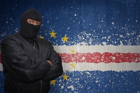 dangerous man: dangerous man in a mask standing near a wall with painted national flag of cape verde