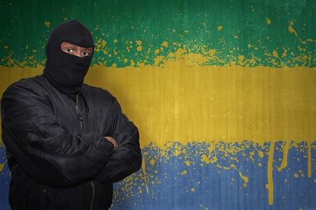 gabon: dangerous man in a mask standing near a wall with painted national flag of gabon Stock Photo