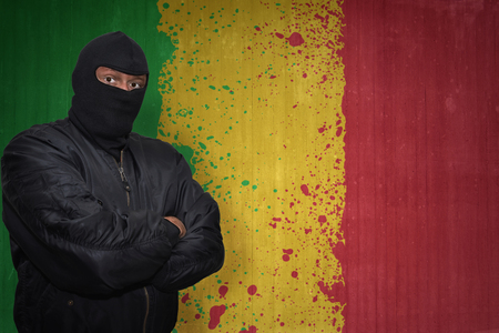 bamako: dangerous man in a mask standing near a wall with painted national flag of mali