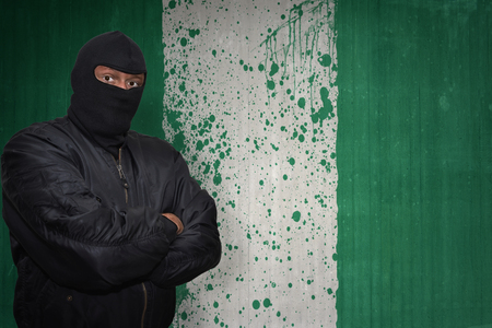 dangerous man in a mask standing near a wall with painted national flag of nigeria