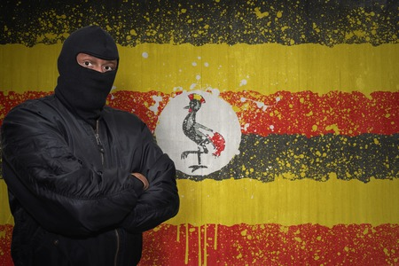 kampala: dangerous man in a mask standing near a wall with painted national flag of uganda