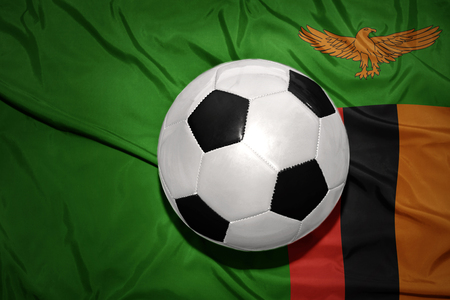 zambian flag: vintage black and white football ball on the national flag of zambia