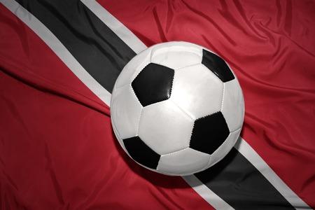 national flag trinidad and tobago: vintage black and white football ball on the national flag of trinidad and tobago