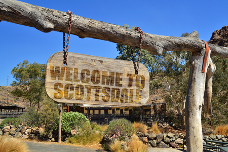 old wood signboard with text  welcome to Scottsdale hanging on a branch