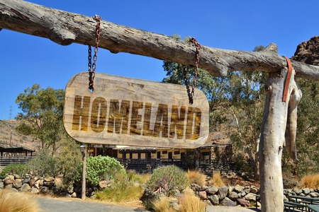 homeland: old wood signboard with text homeland  hanging on a branch
