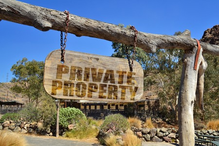 private property: old wood signboard with text private property  hanging on a branch