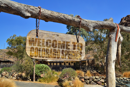 """old vintage wood signboard with text """" welcome to Colorado Springs"""" hanging on a branch"""