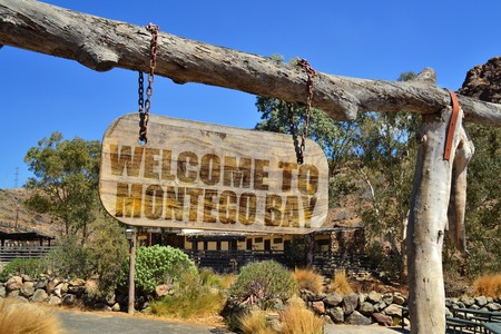 old vintage wood signboard with text  welcome to Montego Bay hanging on a branch