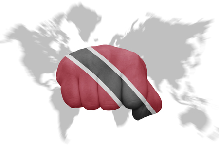 national flag trinidad and tobago: fist with the national flag of trinidad and tobago on a world map background Stock Photo