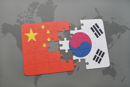 world flag: puzzle with the national flag of china and south korea on a world map background. 3D illustration Stock Photo