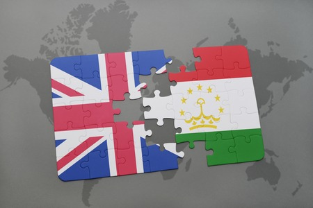 economy of tajikistan: puzzle with the national flag of great britain and tajikistan on a world map background. Stock Photo