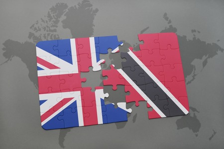 national flag trinidad and tobago: puzzle with the national flag of great britain and trinidad and tobago on a world map background. Stock Photo