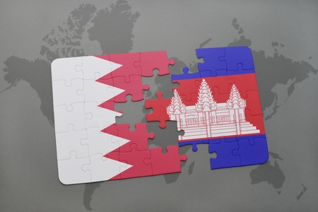 cambodian: puzzle with the national flag of bahrain and cambodia on a world map background. 3D illustration Stock Photo