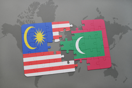 maldives island: puzzle with the national flag of malaysia and maldives on a world map background. 3D illustration Stock Photo