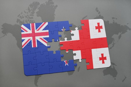 separatism: puzzle with the national flag of new zealand and georgia on a world map background. 3D illustration