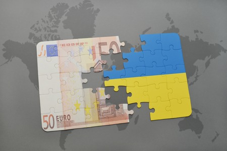 ukrainian flag: puzzle with the national flag of ukraine and euro banknote on a world map background. 3D illustration