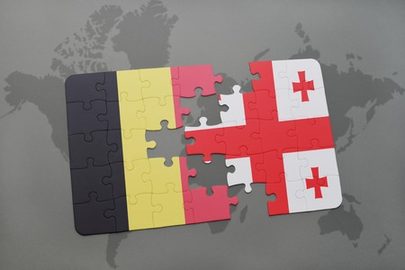 georgian: puzzle with the national flag of belgium and georgia on a world map background. 3D illustration