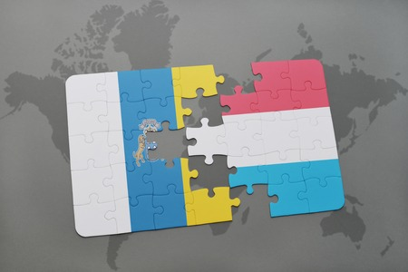 canary: puzzle with the national flag of canary islands and luxembourg on a world map background. 3D illustration