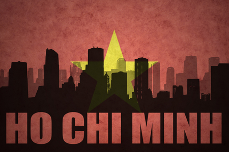 chi: abstract silhouette of the city with text Ho Chi Minh at the vintage vietnamese flag background
