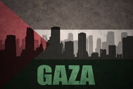 gaza: abstract silhouette of the city with text Gaza at the vintage palestinian flag background