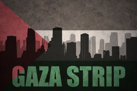 gaza: abstract silhouette of the city with text Gaza Strip at the vintage palestinian flag background