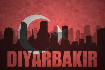 middle east conflict: abstract silhouette of the city with text Diyarbakir at the vintage turkish flag background