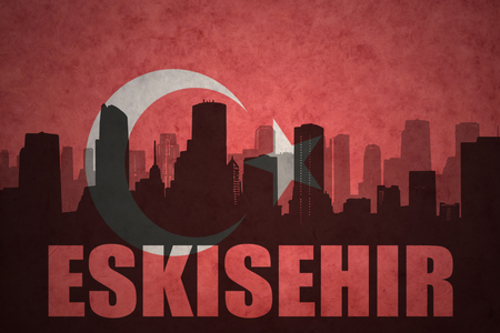 middle east conflict: abstract silhouette of the city with text Eskisehir at the vintage turkish flag background Stock Photo