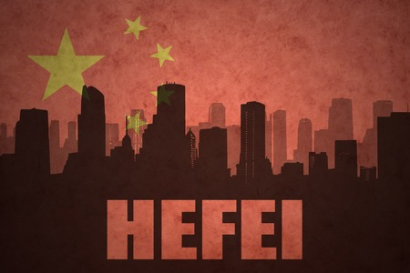 clash: abstract silhouette of the city with text Hefei at the vintage chinese flag background