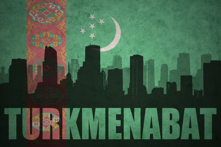 clash: abstract silhouette of the city with text Turkmenabat at the vintage turkmenistan flag background