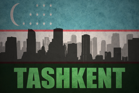 abstract silhouette of the city with text Tashkent at the vintage uzbekistan flag background Stock Photo