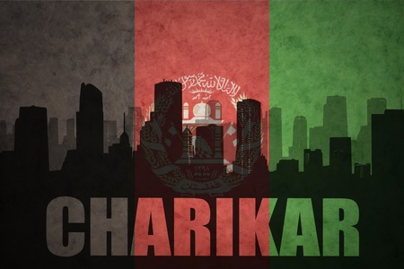 middle east conflict: abstract silhouette of the city with text Charikar at the vintage afghanistan flag background
