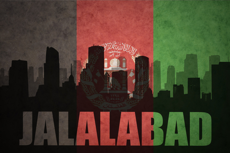 middle east conflict: abstract silhouette of the city with text Jalalabad at the vintage afghanistan flag background