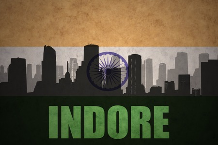 indore: abstract silhouette of the city with text Indore at the vintage indian flag background