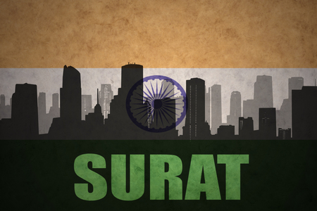 surat: abstract silhouette of the city with text Surat at the vintage indian flag background