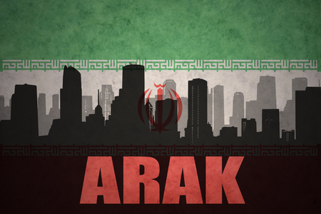 middle east conflict: abstract silhouette of the city with text Arak at the vintage iranian flag background