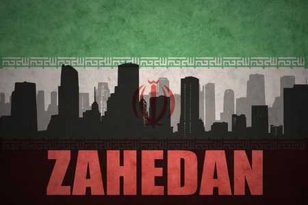 iranian: abstract silhouette of the city with text Zahedan at the vintage iranian flag background Stock Photo