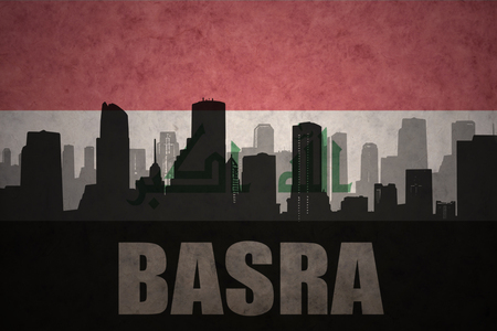 basra: abstract silhouette of the city with text Basra at the vintage iraqi flag background
