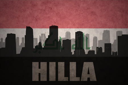 middle east conflict: abstract silhouette of the city with text Hilla at the vintage iraqi flag background