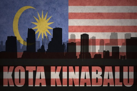 kota kinabalu: abstract silhouette of the city with text Kota Kinabalu at the vintage malaysian flag background