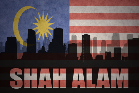 shah: abstract silhouette of the city with text Shah Alam at the vintage malaysian flag background