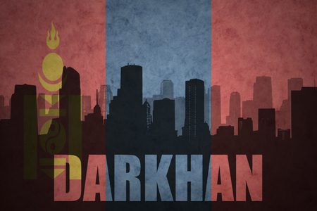 clash: abstract silhouette of the city with text Darkhan at the vintage mongolian flag background