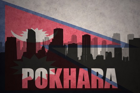 pokhara: abstract silhouette of the city with text Pokhara at the vintage nepal flag background Stock Photo