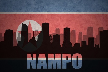 clash: abstract silhouette of the city with text Nampo at the vintage north korea flag background