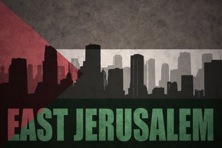 middle east conflict: abstract silhouette of the city with text East Jerusalem at the vintage palestinian flag background