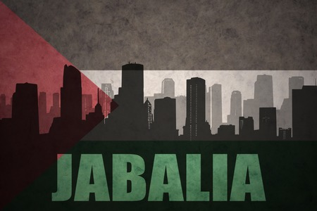 middle east conflict: abstract silhouette of the city with text Jabalia at the vintage palestinian flag background Stock Photo