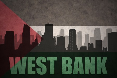 west bank: abstract silhouette of the city with text West Bank at the vintage palestinian flag background