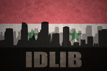 middle east conflict: abstract silhouette of the city with text Idlib at the vintage syrian flag background