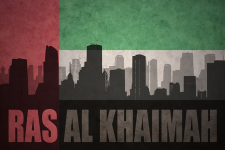 ras: abstract silhouette of the city with text Ras Al Khaimah at the vintage united arab emirates flag background