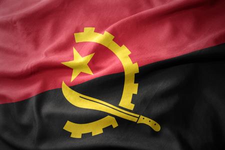 agitando la bandera nacional de colores de angola.
